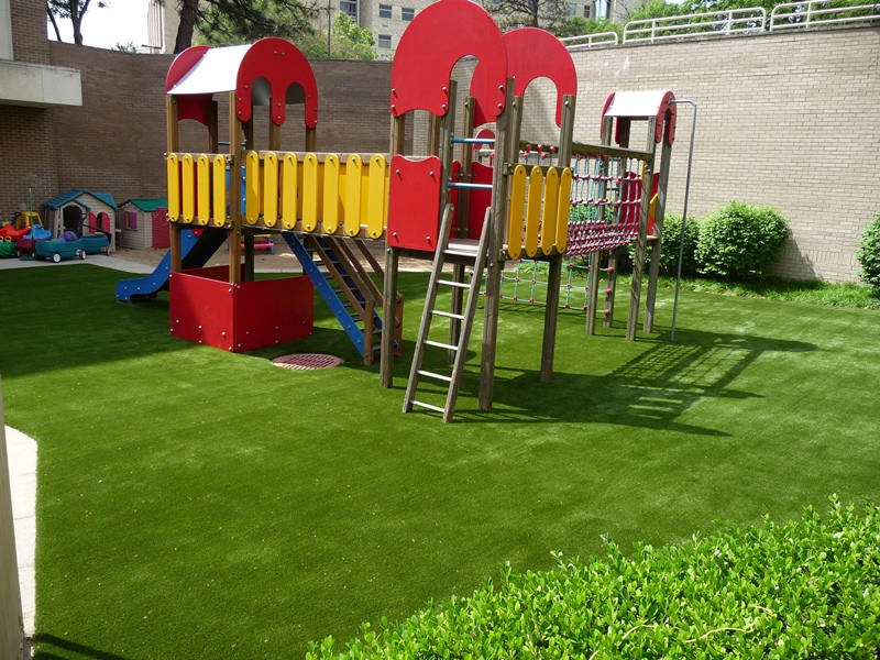 Child playset on artificial playground turf in Missouri