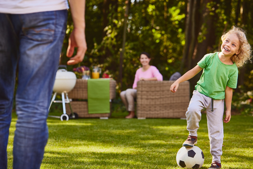 Child plays soccer with his dad on artificial grass in the backyard